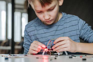 Boy assembling robot at home - EYAF00944