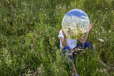 Woman sitting in meadow, hiding behind mirror, reflecting nature - PSTF00597