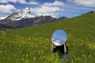 Woman sitting in meadow, hiding behind mirror, reflecting the mountains of Val Badia, Alto Adige, Italy - PSTF00600