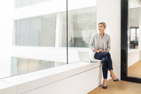 Blond businesswoman with laptop, sitting on windowsill in office building - PESF01848