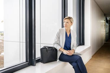 Blond businesswoman with laptop, sitting on windowsill in office building - PESF01863