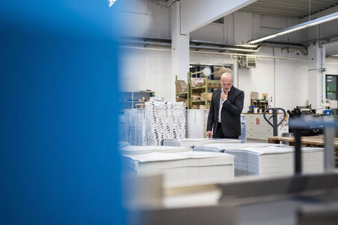 Businessman in a printing plant checking product - DIGF09316