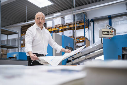 Businessman in a printing plant holding paper - DIGF09328