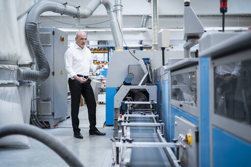 Businessman standing at a machine in a factory - DIGF09334