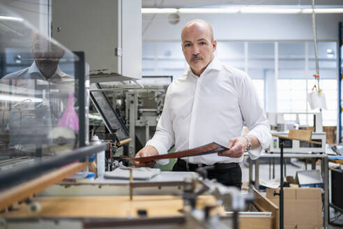 Businessman in a printing plant checking product - DIGF09340