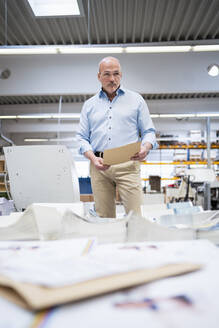 Businessman in a printing plant checking product - DIGF09346