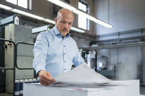 Businessman in a printing plant checking product - DIGF09364