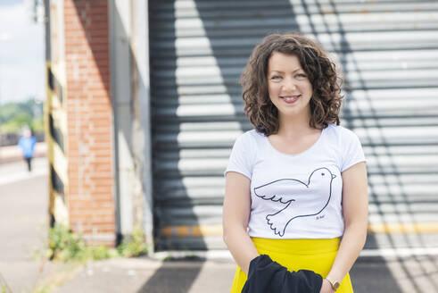 Portrait of smiling brunette woman at roller shutter - HBIF00053