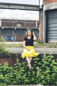 Happy woman sitting on a plant covered wall in an old industrial area - HBIF00056