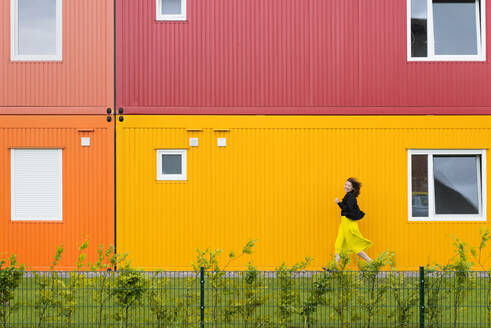 Woman running in front of a colorful two-story container building - HBIF00059