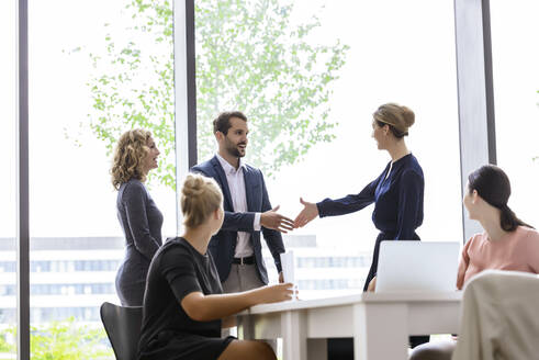 Businesswoman greeting colleagues in her team - BMOF00225
