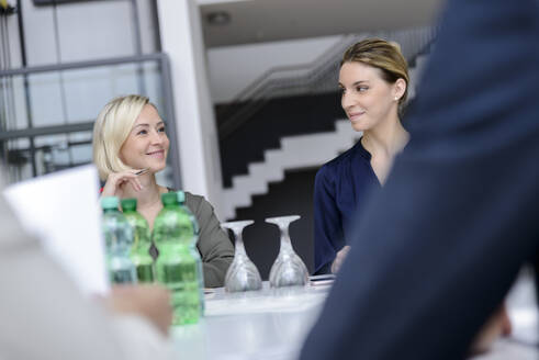 Confident businesswomen in a meeting, smiling - BMOF00252