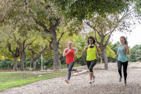 Three sporty young women running in a park - DLTSF00567