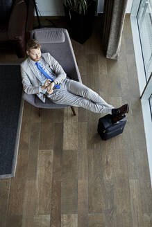 Businessman relaxing in hotel lobby checking the time - ZEDF03072