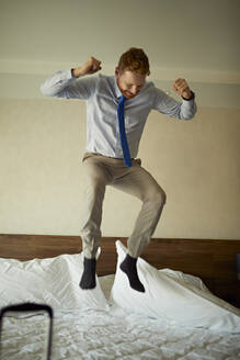 Excited businessman jumping on bed in hotel room - ZEDF03111