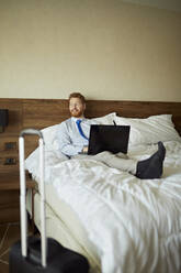 Businessman lying on bed in hotel room using laptop - ZEDF03114