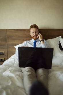 Businessman lying on bed in hotel room using laptop and cell phone - ZEDF03117