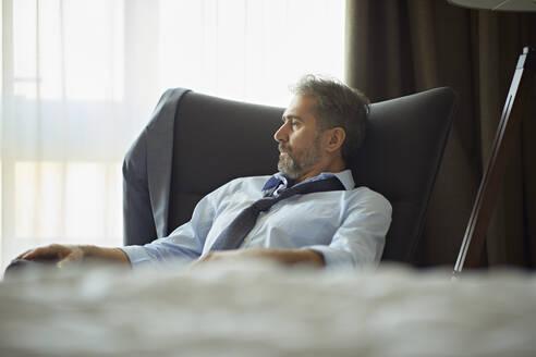 Businessman sitting in armchair in hotel room - ZEDF03129