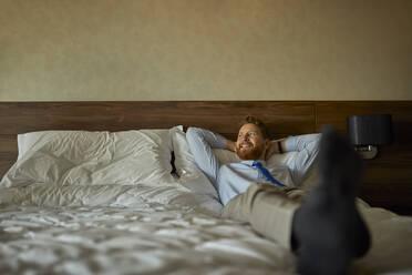 Businessman lying on bed in hotel room - ZEDF03150