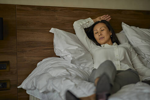 Businesswoman lying on bed in hotel room with closed eyes - ZEDF03165