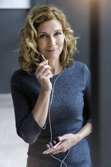Portrait of blond businesswoman with earphones and smartphone in office - BMOF00269