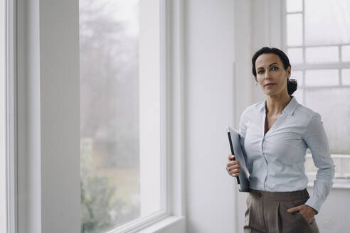 Successful businesswoman, standing by window, carrying laptop - JOSEF00034
