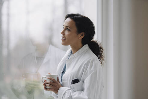 Female doctor looking out of window, holding cup of coffee - JOSEF00097