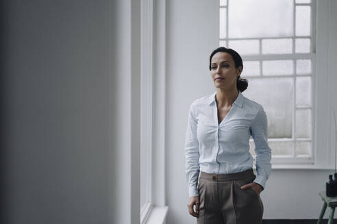 Successful businesswoman, standing by window, with hand in pocket - JOSEF00100