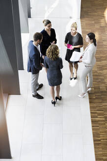 Business people standing in modern office building discussing project - BMOF00291