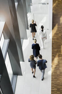Business people walking in modern office building - BMOF00297