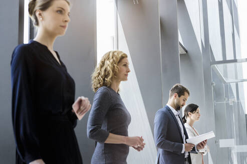 Businesswomen and businessmen waiting in line in the office - BMOF00300