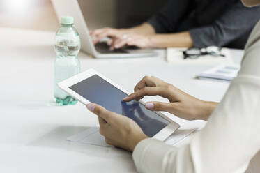 Close-up of businesswoman using tablet during a meeting in office - BMOF00306