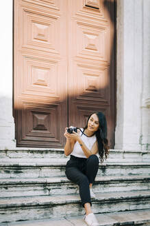 Portrait of fashionable young woman sitting on stairs taking pictures with camera, Lisbon, Portugal - DCRF00013