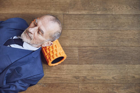 Senior businessman relaxing on wooden floor, resting on fascia roll - MCF00617