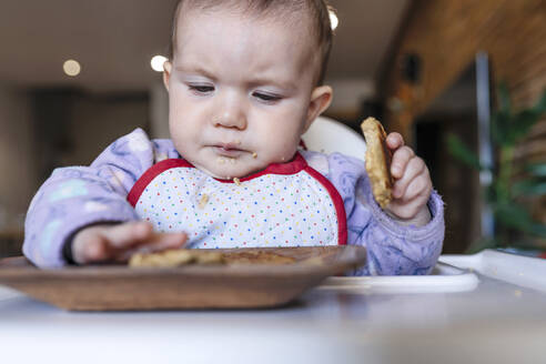 Portrait of baby girl sitting in high chair eating homemade oatmeal cookies with hands - GEMF03461