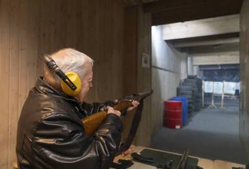 Senior man aiming with a gun in shooting range - AHSF01968