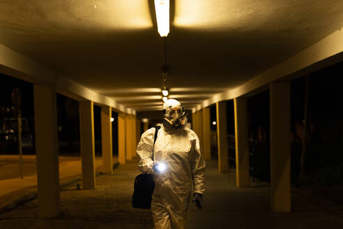 Senior woman wearing protective suit and mask in the city at night - ERRF02760