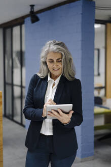 Grey-haired businesswoman using tablet in a loft office - GUSF03346