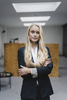 Portrait of a confident young businesswoman in loft office - GUSF03400