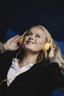 Portrait of a smiling young businesswoman listening to music with headphones - GUSF03436