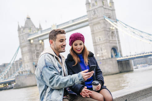 Two young tourists sitting on wall, using smartphone, with  London Bridge in background - DGOF00502