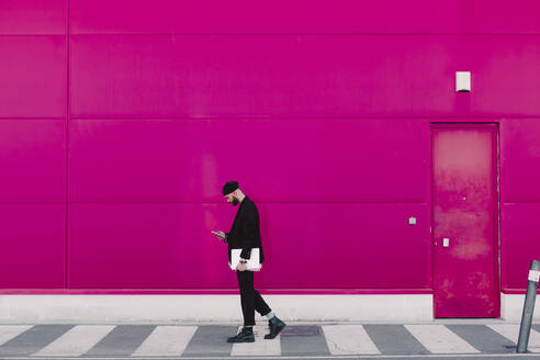 Businessman with smartphone and documents walking along a pink wall - ERRF02779