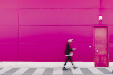 Young man with headphones walking along a pink wall, blurred - ERRF02782
