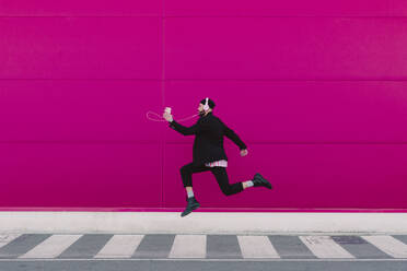 Young man listening to music and jumping in front of a pink wall - ERRF02788