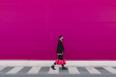 Young man walking with travelling bag in front of a pink wall - ERRF02791