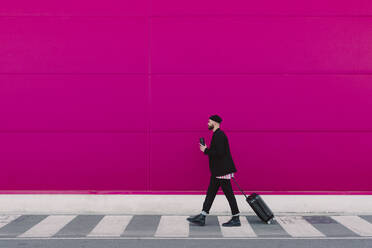 Young man with trolley walking along a pink wall, holding reusable cup - ERRF02797