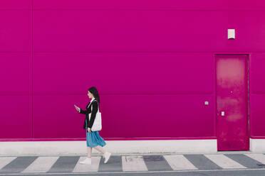Young woman walking along pink wall, using smartphone - ERRF02800