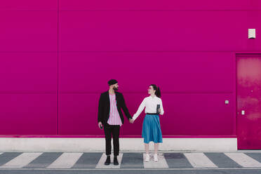 Couple standing on crosswalk, face to face and holding hands - ERRF02806