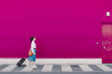Young woman using smartphone and walking with trolley along a pink wall - ERRF02809