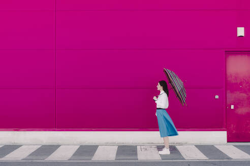 Young woman with umbrella in front of a pink wall - ERRF02812